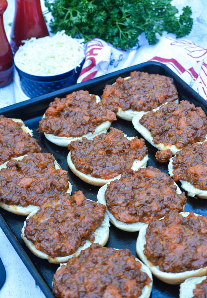 cafeteria style pizza burgers arranged on a large, dark metal baking pan