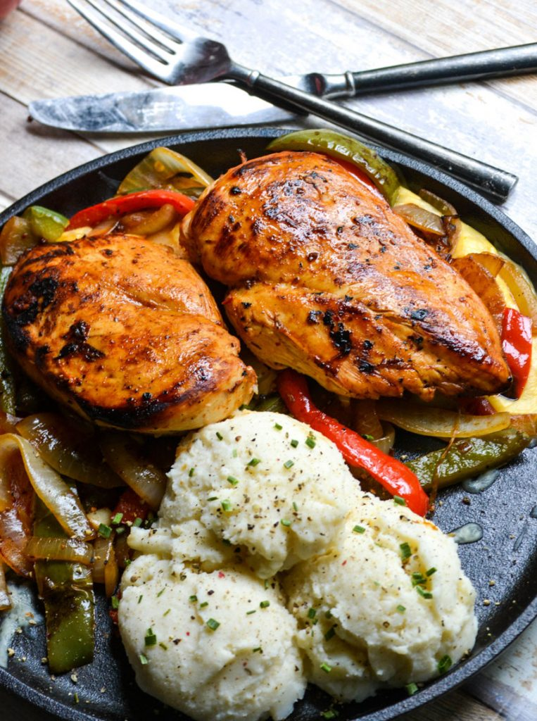 copycat TGIFriday's sizzlin chicken & cheese on a flat cast iron skillet next to a pair of silverware
