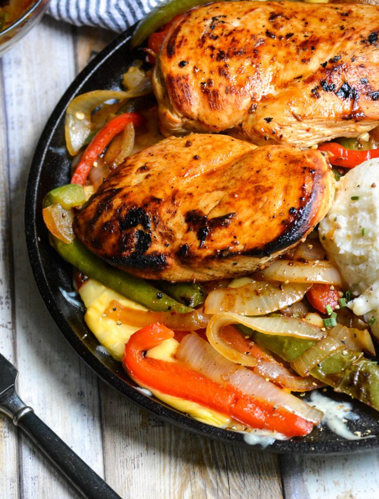 copycat TGIFriday's sizzlin chicken & cheese on a flat cast iron skillet