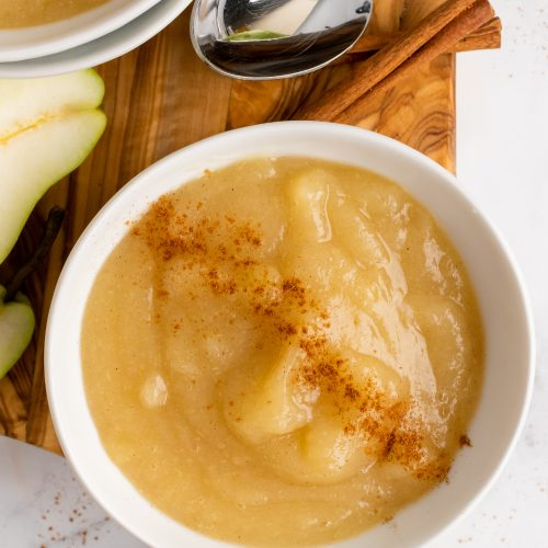 Instant pot pear sauce served in a white bowl & sprinkled with ground cinnamon