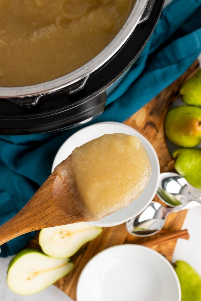 a wooden spoon holding a scoop of instant pot pear sauce above a pressure cooker