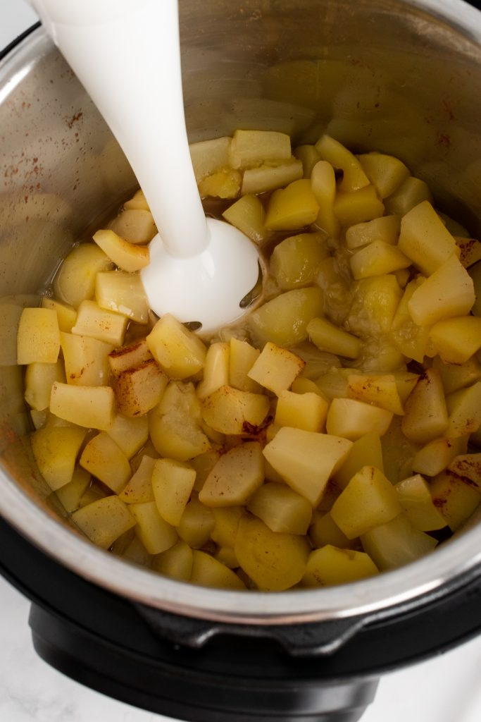 a white immersion blender in steamed apples in an instant pot
