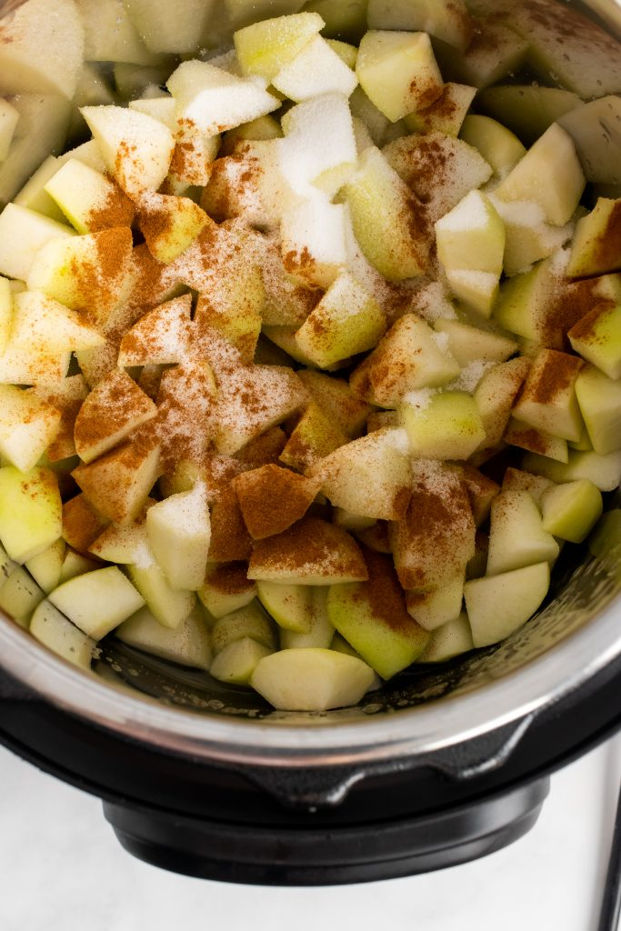 diced apples sprinkled with ground cinnamon in the bowl of an Instant Pot