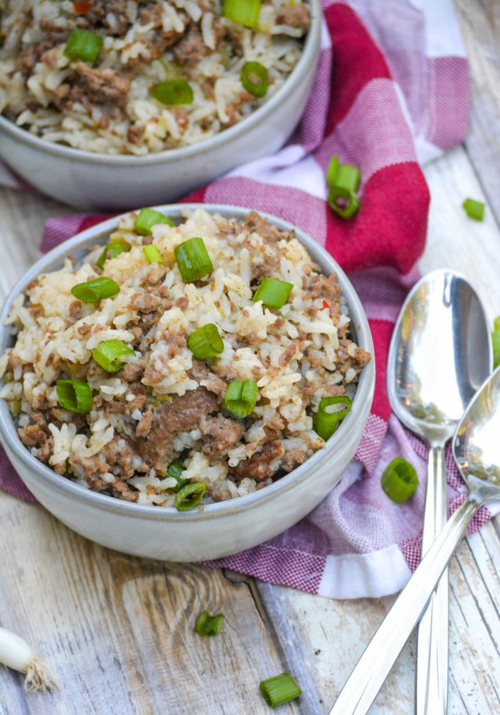 two gray bowls filled with ground beef, sausage & rice casserole topped with sliced green onions