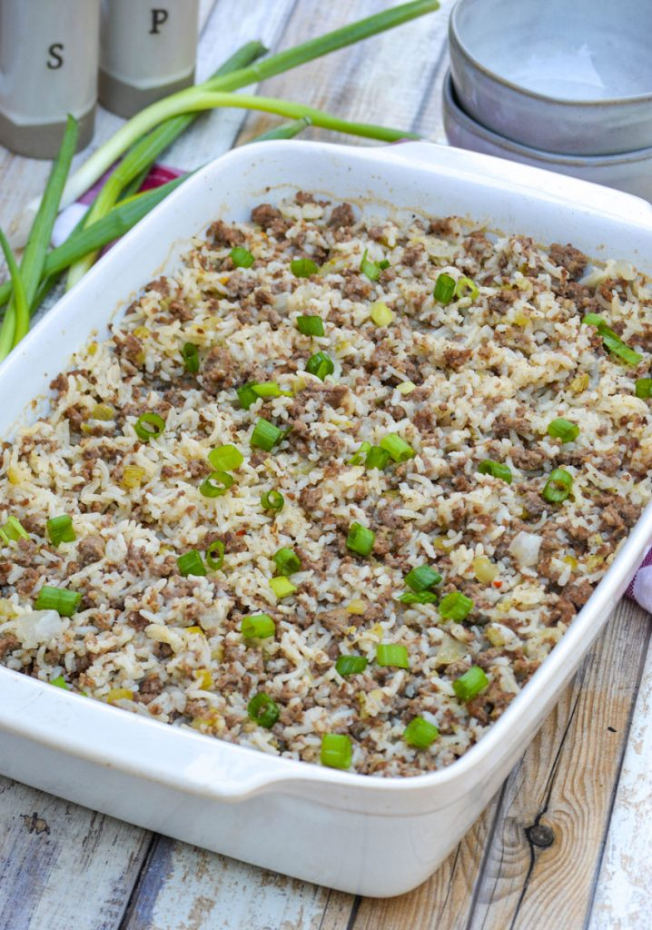 """ground beef, sausage, and rice casserole in a 9x13"""" white casserole dish"""