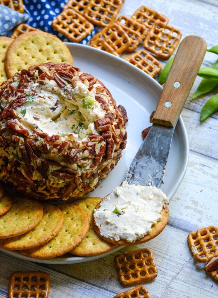 a cracker on the edge of an appetizer plate spread with a seasoned cream cheese mixture from a savory cheeseball