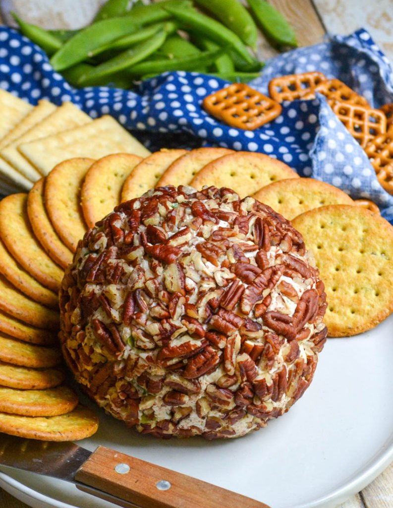 savory pecan crusted cheeseball on a white plate surrounded by crackers