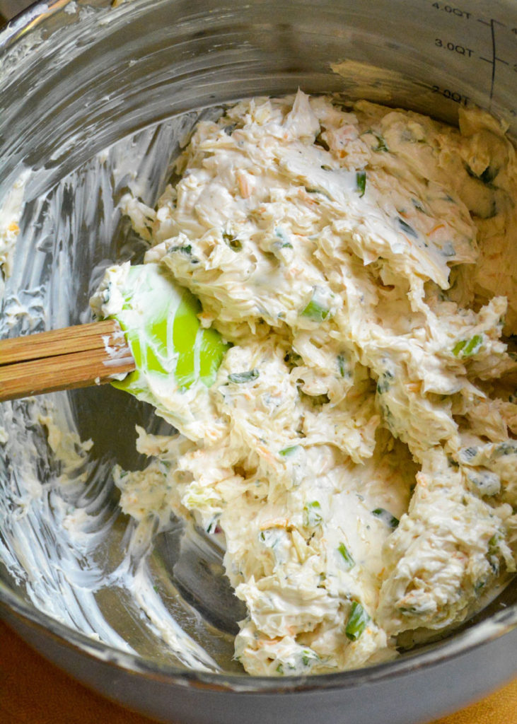 ingredients for a basic cheeseball recipe mixed together with a spatula in a large mixing bowl