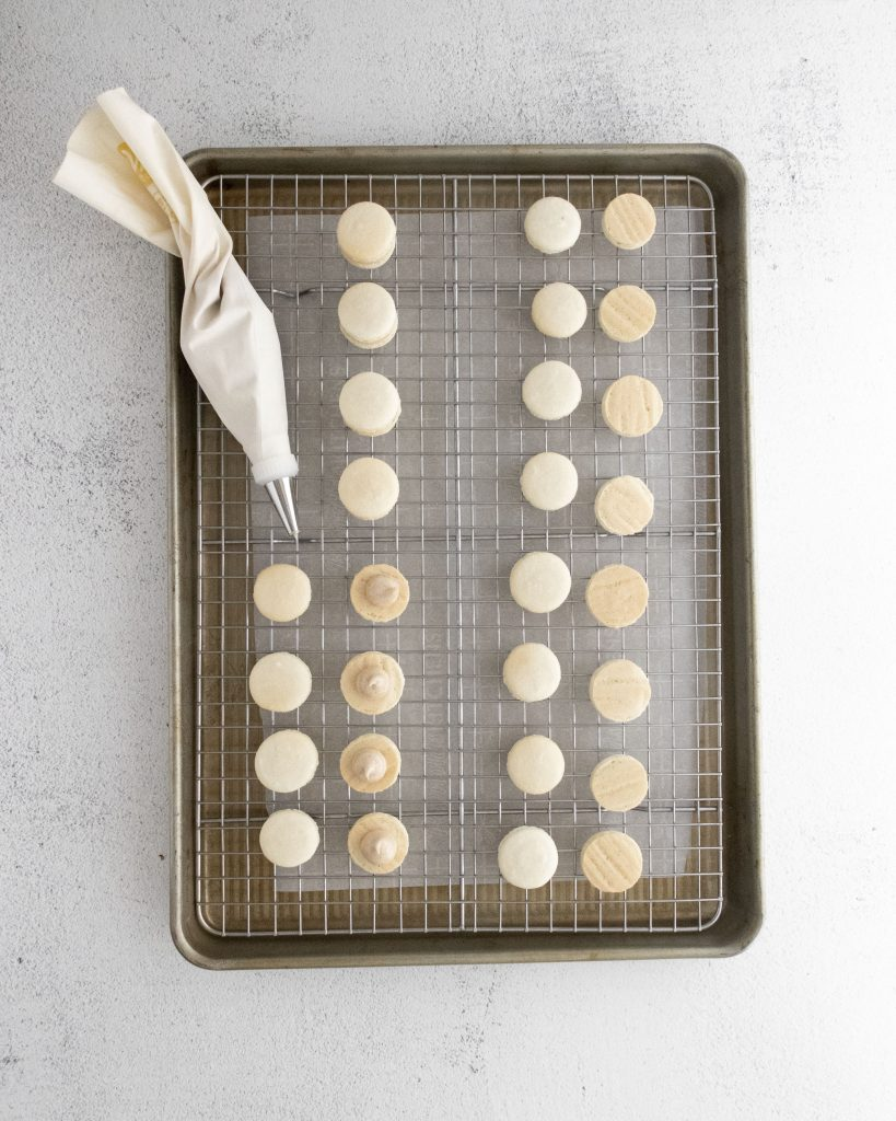 macaron shells piped with filling on a cooling wrack