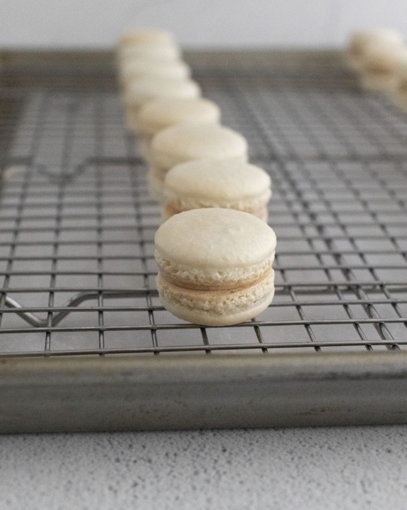 white macarons shown on a metal cooling wrack