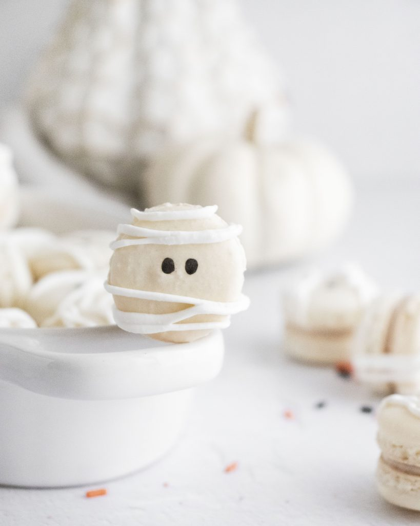 mummy macarons stacked in a white serving dish