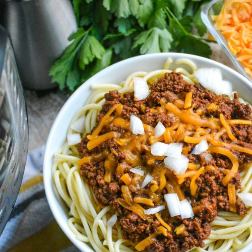 Cincinnati chili served over spaghetti pasta in a white bowl & topped with melted cheddar and diced white onion