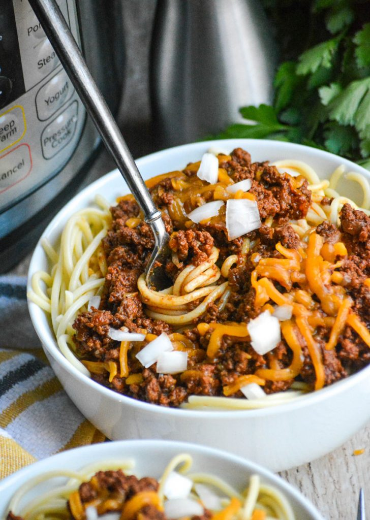 a silver fork twirling spaghetti pasta tossed with Cincinnati chili